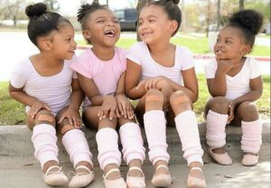 3 little black girls sitting and laughing on the curb